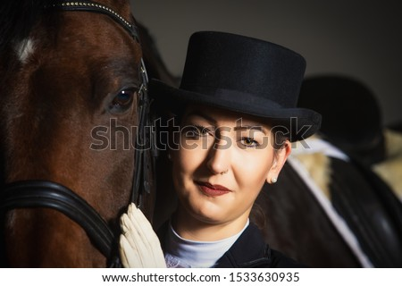 Young woman in tails in portraits next to her horse. She is holding her head next to the one of the horse and is looking into the camera. #1533630935