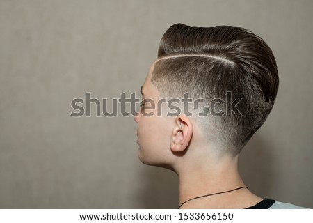 Stylish modern retro haircut side part with mid fade with parting of school boy guy in a barbershop on a brown background Royalty-Free Stock Photo #1533656150