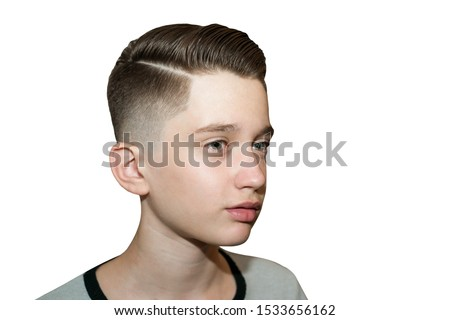 Stylish modern retro haircut side part with mid fade with parting of a schoolboy guy in a barbershop on isolated white background Royalty-Free Stock Photo #1533656162