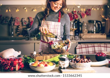 Young Woman Cooking in the kitchen. Healthy Food for Christmas (stuffed duck or Goose) #1533662345