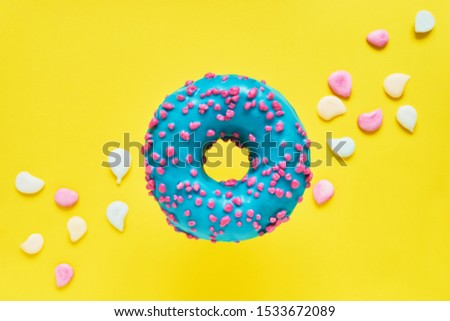 Sprinkled Blue Donut. Glazed sprinkled donut on bright yellow background with colorful candies. Top view, copy space #1533672089