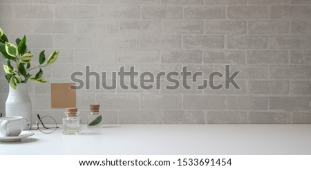 Minimal workspace with copy space and office supplies on white desk and grey brick wall background