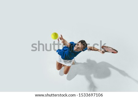 Young woman in blue shirt playing tennis. She hits the ball with a racket. Indoor studio shot isolated on white. Youth, flexibility, power and energy. Negative space. Top view. Royalty-Free Stock Photo #1533697106