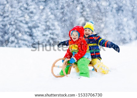 Little girl and boy enjoying sleigh ride. Child sledding. Toddler kid riding a sledge. Children play outdoors in snow. Kids sled in snowy park in winter. Outdoor fun for family Christmas vacation. #1533706730