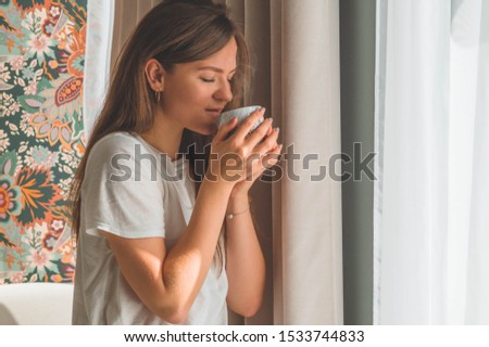 Woman with cup of hot drink by the window. Looking at window and drink tea. Good morning with tea. Autumn Winter Time. Cozy home.  #1533744833