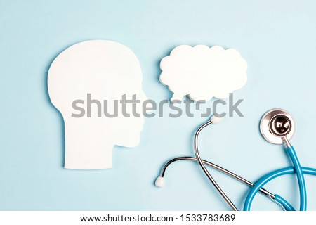 Head silhouette with speech bubble and stethoscope on bluer background. Empty speech bubble with place for text.