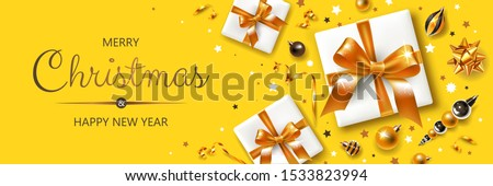 Horizontal banner with gold and silver Christmas symbols and text. Gifts, decoration and other festive elements on yellow background. #1533823994