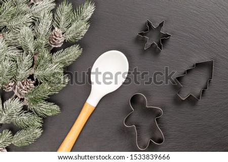Gingerbread man, fir, snowflake cookie cutters and white wooden spoon for Christmas cooking or baking with snowy fir branches with cones over slate background. Flat lay, top view. #1533839666