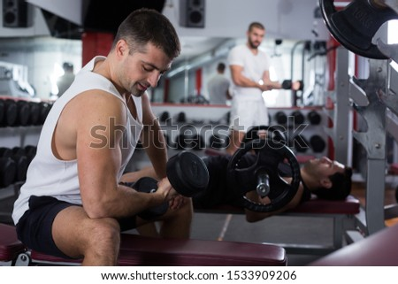 Concentrated sporty guy during workout in gym with dumbbells #1533909206