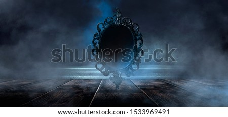 Dark night magic scene. Magic old mirror in a metal frame on a wooden tabletop. Smoke, magic, magical experience, a fabulous night. Blue neon, moonlight at night. #1533969491