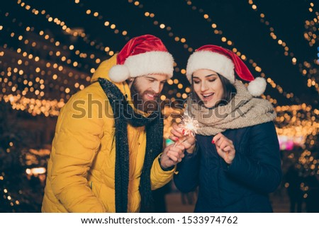 Photo of funny couple guy lady two people at x-mas celebration park sharing fire magic sparklers outdoors newyear party wearing warm coats santa caps scarfs gloves outside #1533974762