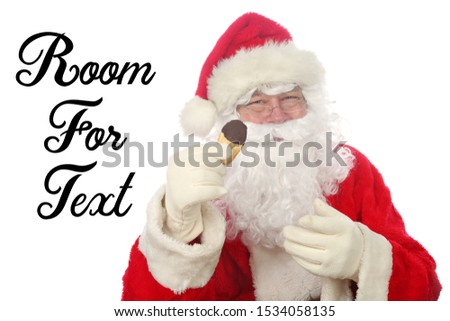 Santa Claus. Santa Claus aka Chris Kringle enjoys Cookies and Milk left for him one Christmas Eve. Isolated on white. Room for text.   #1534058135