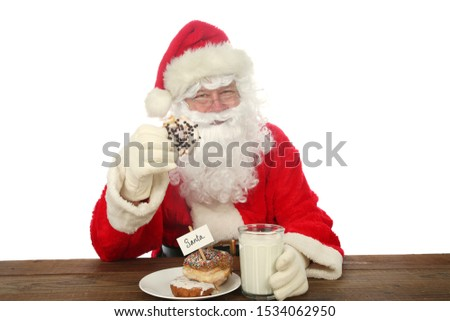 Santa Claus. Santa Claus aka Chris Kringle enjoys Donuts and Milk left for him one Christmas Eve. Isolated on white. Room for text.   #1534062950