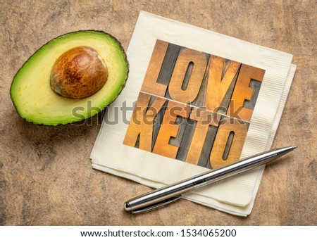 love keto, high fat ketogenic diet concept - word abstract in vintage letterpress wood type on a napkin with a cut avocado #1534065200