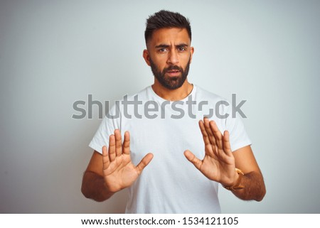 Young indian man wearing t-shirt standing over isolated white background Moving away hands palms showing refusal and denial with afraid and disgusting expression. Stop and forbidden.