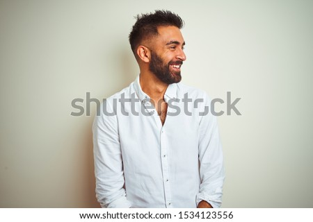 Young indian man wearing elegant shirt standing over isolated white background looking away to side with smile on face, natural expression. Laughing confident. #1534123556