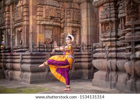 Indian classical odissi dancer at Brahmesvara Temple with sculptures in bhubaneswar, odisha, India #1534131314