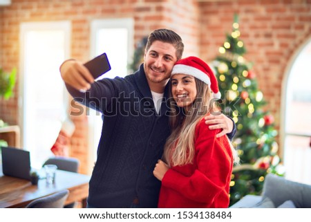 Young beautiful couple smiling happy and confident. Standing and hugging make selfie by camera around christmas tree at home #1534138484