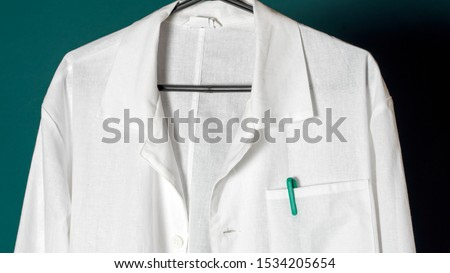 Closeup of a doctor's white lab coat on a hanger against a dark background. #1534205654