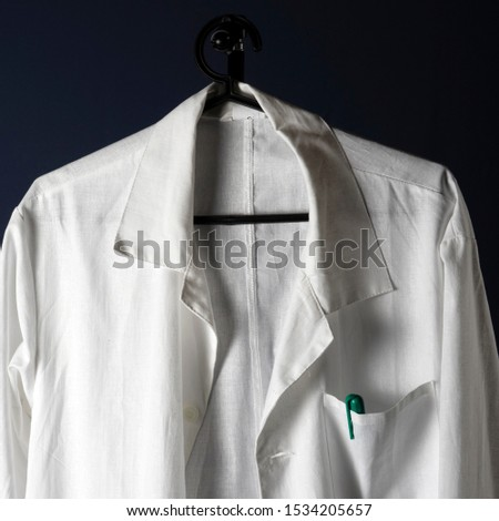 Closeup of a doctor's white lab coat on a hanger against a dark background. #1534205657