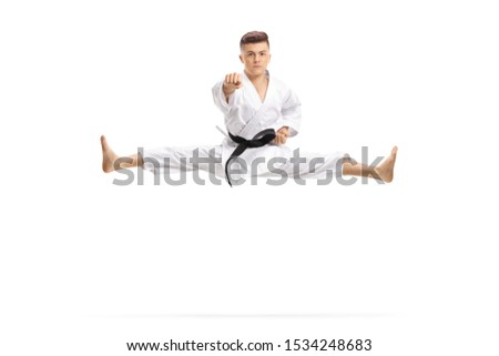 Guy in kimono jumping and doing martial art split isolated on white background Royalty-Free Stock Photo #1534248683