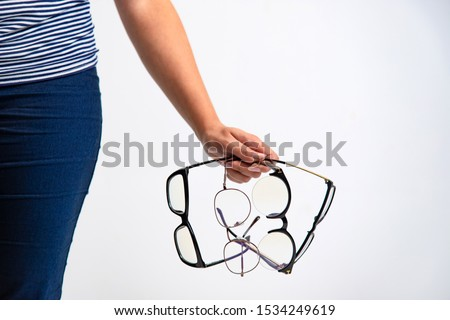 Spectacles closeup. Woman hand holds black framed eyeglasses. Four pairs of modern glasses. #1534249619