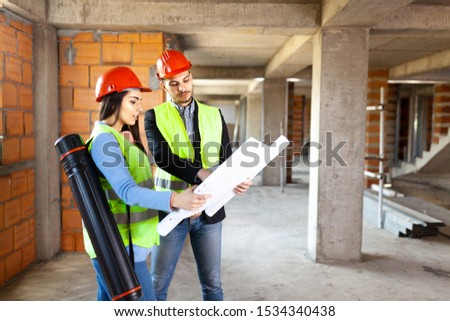 architects with blueprints. construction site engineers with project. satisfied expressions #1534340438