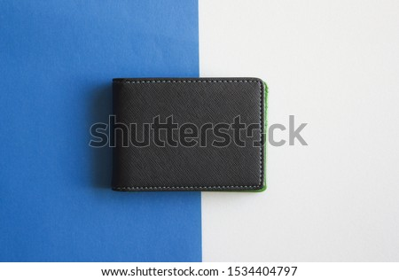 Black wallet isolated on white and blue background . Closed wallet .  Royalty-Free Stock Photo #1534404797