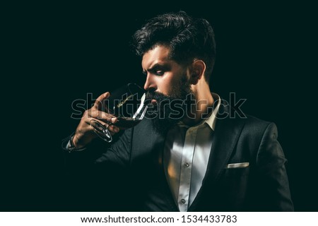 Cheerful bearded man is drinking expensive cognac. Old traditional whiskey drink - gentlemen beverage. Elegant and stylish man in classical wear holding glass with cognac in hand Royalty-Free Stock Photo #1534433783