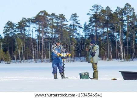 fisherman drills ice drill in winter winter sport winter fishing #1534546541