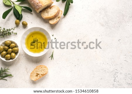 Olive Oil and Bread. Organic olive oil with green olives in bowl, herbs and ciabatta bread on white background with copy space, healthy mediterranean food concept. #1534610858