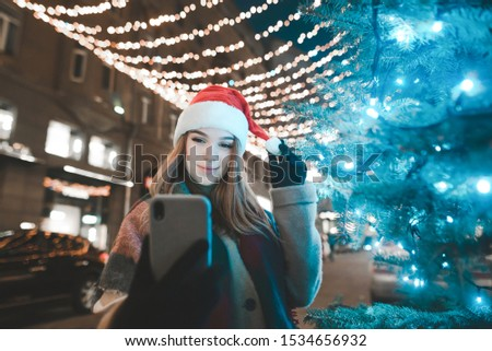 Girl in a Santa hat stands on a decorated street in a town with a smartphone in hand and takes a selfie near a decorated Christmas tree, smiling and looking into the camera of a smartphone. New Year #1534656932