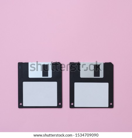 Two black floppy disks on a pink background. #1534709090