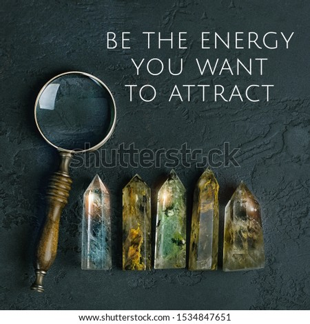 magnifying glass and quartz stones mineral. be the energy you want to attract - inspiration quote. healing gemstones crystal for relaxation on black background #1534847651