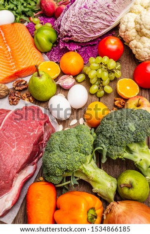 Trending paleo/pegan diet. Healthy balanced food concept. Set of fresh products, raw meat, salmon, vegetables and fruits. Old wooden boards background #1534866185