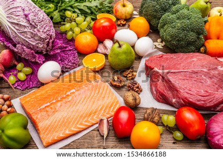 Trending paleo/pegan diet. Healthy balanced food concept. Set of fresh products, raw meat, salmon, vegetables and fruits. Old wooden boards background #1534866188