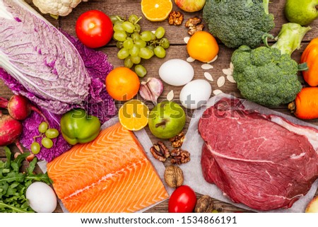 Trending paleo/pegan diet. Healthy balanced food concept. Set of fresh products, raw meat, salmon, vegetables and fruits. Old wooden boards background, top view #1534866191