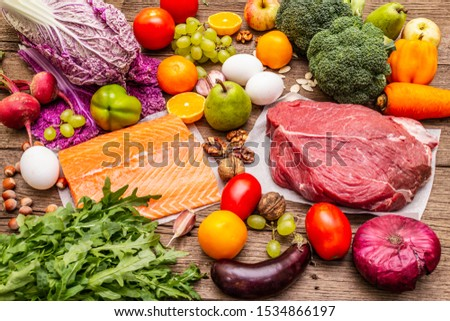 Trending paleo/pegan diet. Healthy balanced food concept. Set of fresh products, raw meat, salmon, vegetables and fruits. Old wooden boards background #1534866197