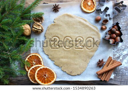 Text 2020. Concept of the new year 2020. Christmas pastries. Homemade cakes or cookies for the new year and Christmas.Spices, nuts, dried oranges, fir branches, wooden background. Rustic style. New ye #1534890263