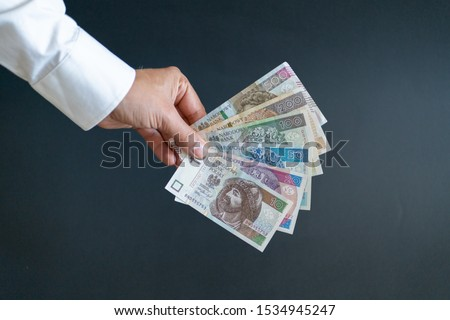 Polish zlotys. The man is holding various banknotes. Polish currency. #1534945247