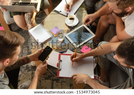 Group of young caucasian office workers meeting to discuss new ideas. Creative meeting. Teamwork and brainstorming. Men and women meet in office to plan their future working. Business concept. #1534973045
