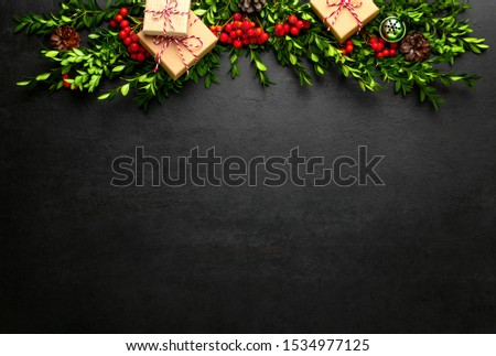 Noel or Christmas dark background with gift boxes and natural winter holidays traditional botany decor such as red berries and evergreen branches arranged in a header, flat lay composition  #1534977125