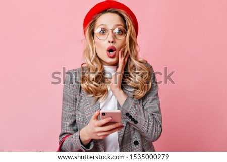 Close-up shot of blue-eyed girl with eyeglasses shocked looking at camera with phone in her hands. Curly lady in red beret posing on pink background #1535000279