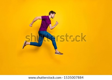 Full length body size side profile photo of fast quick handsome man wearing blue pants trousers footwear running jumping to empty space isolated over vivid color background
