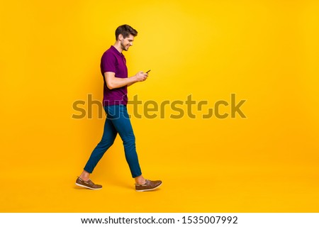 Full length body size profile side view of his he nice attractive cheerful cheery glad addicted guy using digital device 5g smm walking isolated over bright vivid shine vibrant yellow color background