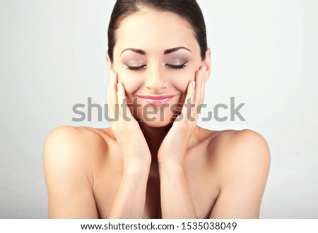 Beautiful young woman touching herself fresh face skin. Smiling female model applying skincare moisturizer. Beauty and anti aging treatment. Closeup with empty copy space. Front view #1535038049