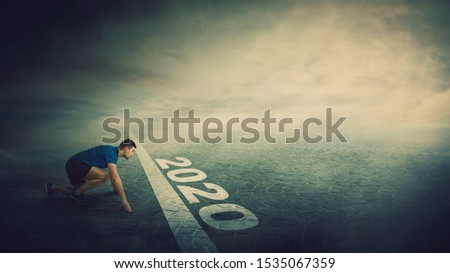 Determined man stands in running position, at the start line, looking ahead confident. Guy sprinter ready for starting 2020 new year challenges. Competitive winner behaviour and motivation concept. Royalty-Free Stock Photo #1535067359