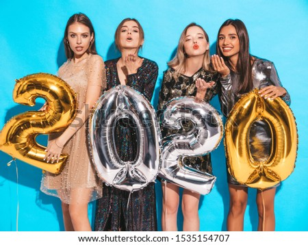 Beautiful Women Celebrating New Year. Happy Gorgeous Girls In Stylish Sexy Party Dresses Holding Gold and Silver 2020 Balloons, Having Fun At New Year's Eve Party. Holiday Celebration.Charming Models  #1535154707