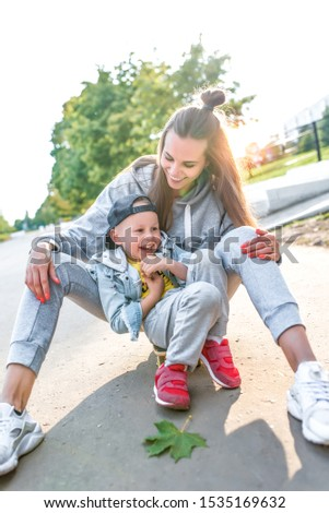 Happy laugh, Mom woman with little boy son of 3-5 years old, having fun enjoying rest, summer autumn in city park. Casual wear denim cap, sneaker pants. Skateboard sit skate, mother's day concept. #1535169632