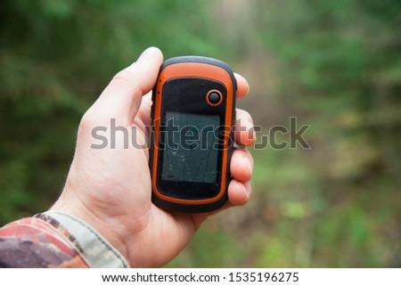 Man's hand holds a GPS navigator. Orientation in the forest using the navigator. Close-up photo of the navigator. #1535196275